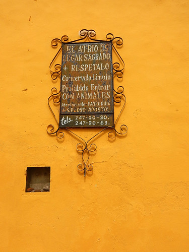 A sign asking people to respect the property, keep it clean and don't enter with animals on the yellow wall of a church in Cholula, Mexico