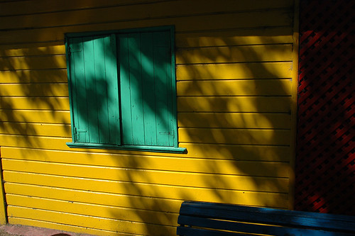 Yellow wall with turquoise shutters in La Boca, Buenos Aires, Argentina