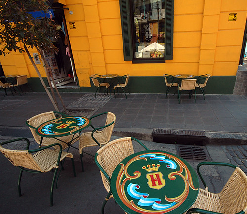 Café with tables painted in the 'filete'-style popular in Buenos Aires in front of a yellow wall in La Boca, Buenos Aires
