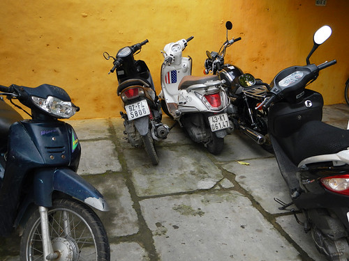 Motorcycles parked against a yellow wall in Hoi An, Vietnam