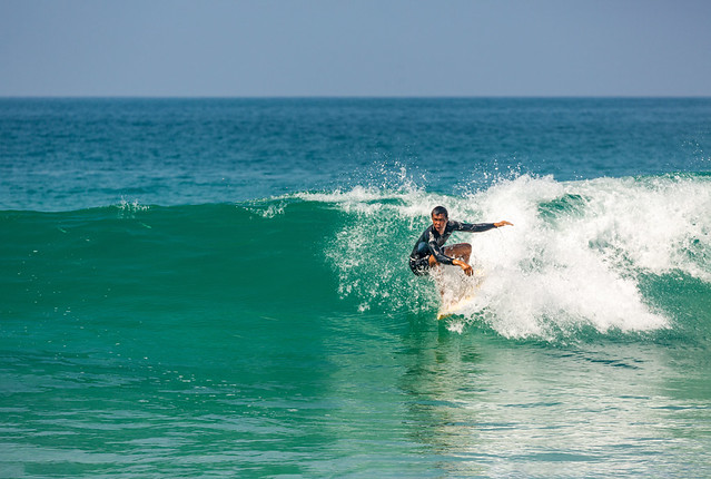 Surfing in the cool waves at Nai Harn Beach, Phuket, Thailand.