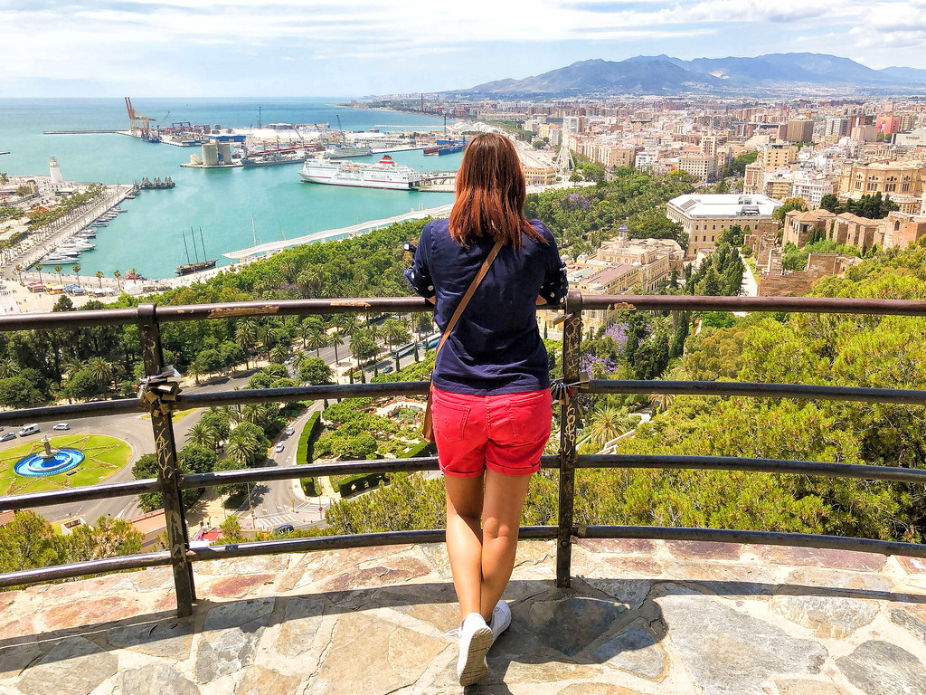 A view over Malaga from Gibralfaro Castle. I am standing in the middle of the photo, wearing a blue tshirt and red shorts, admiring the view
