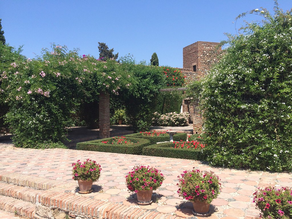An interior courtyard of the Alcazaba. There is an old wall in the back. In the patio there are red flowers and orange trees.