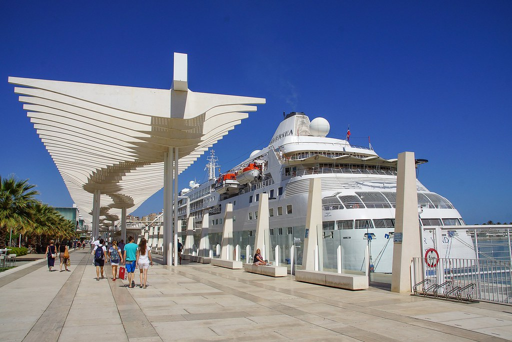 A medium sized white cruise ship is docked next to the Muelle Uno promenade. Many people are walking on the promenade which is covered with parasols to shade from the intense summer sun.