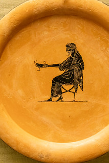 Black-figured plate: Dionysos, god of wine seated holding out a drinking-cup