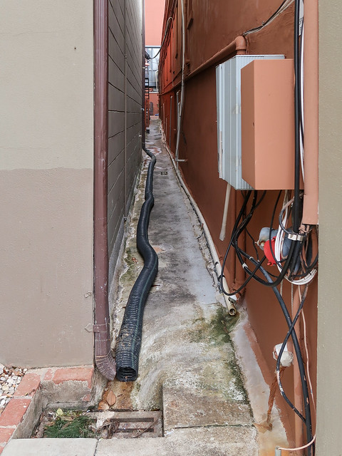 From a downspout to a stormdrain, a long pipe, down a tight-squeeze alley.