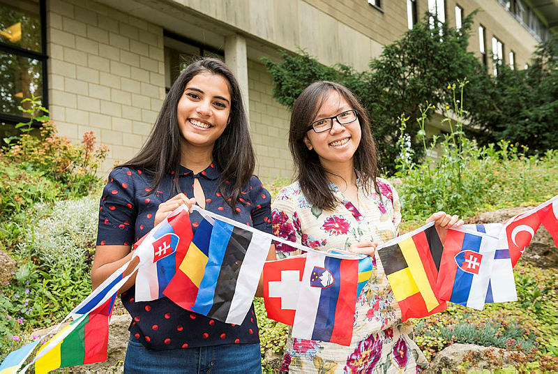 Two students holding different country flags