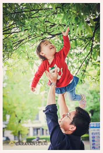 公園 パパの高い高いで木の葉っぱにタッチする女の子