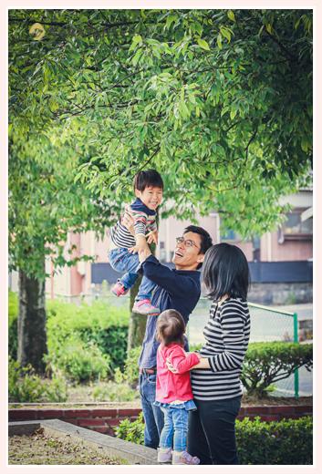 公園でパパに高い高いをしてもらう男の子