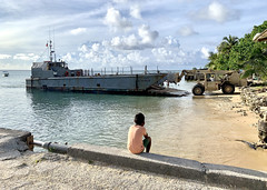 A young Marshall Islander watches as a forklift offloads supplies Seabees are using during a project in Kwajalein Atoll. (U.S. Navy/CE3 Christian Carnate)