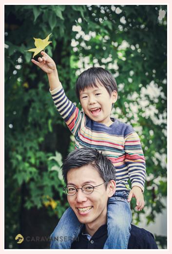 パパのに肩車されカエデの葉をもつ男の子