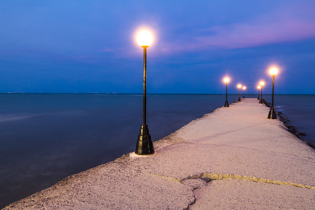Yellow street light and a blue sea and sky during blue hour