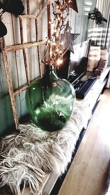 Groene glazen fles op vacht tv meubel landelijk
