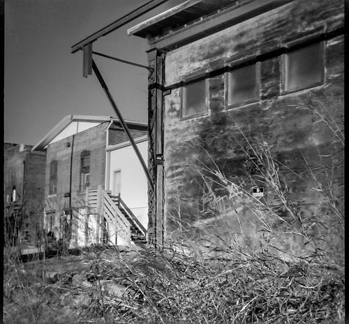 rearfacade industrialarchitecture architecturalforms urbanlandscape urbandecay railroaddistrict asheville northcarolina bencinikoroll aristaedu200 hc110developer 120 120film film 6x6 mediumformat monochrome monochromatic blackandwhite