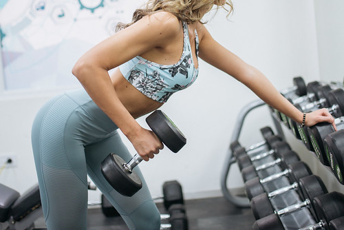 Young sportswoman lifting weights in gym