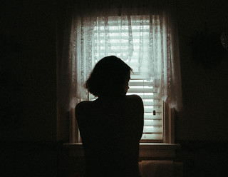 a woman of the cold, lost in the curtains