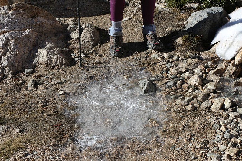 Puddles on the PCT south of Glen Pass are still icy at 7am - Vicki is still wearing her microspikes