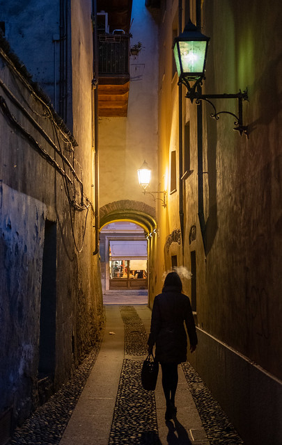 Photo of a dark lantern-lit alley with a woman walking away from the camera, smoking