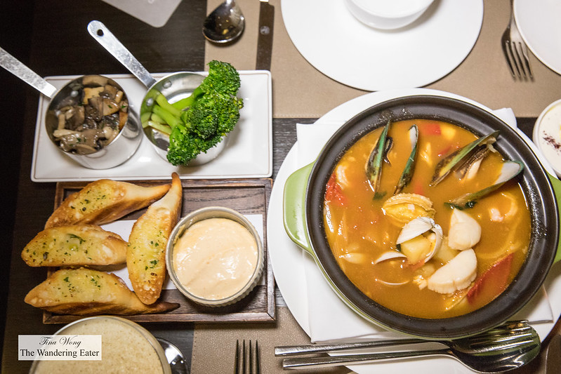 The spread for the Seafood Stew, Abalone - made with clams, haddock, and New Zealand mussels; served with two sides (roast mushrooms and sauteed broccoli) and garlic toasts with aioli on the side