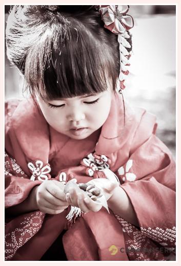 七五三 神社の境内で拾ったドングリを見つめる女の子