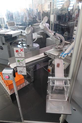 Kleines Stück Lindt Schokolade auf Knopfdruck spendiert vom Roboter in der Produktionsstraße