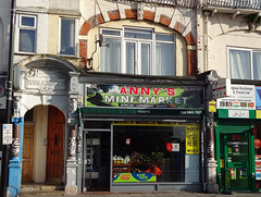 "A ground-floor shop with a sign above reading ""Anny's Mini Market"" over a background showing a green forest canopy.  The fully-glazed shopfront has a couple of decals around the edges advertising money transfer services.  On the first floor above, arched brickwork frames a large window, and to the left is an arched entryway with ""Royal Mansions"" embossed above."
