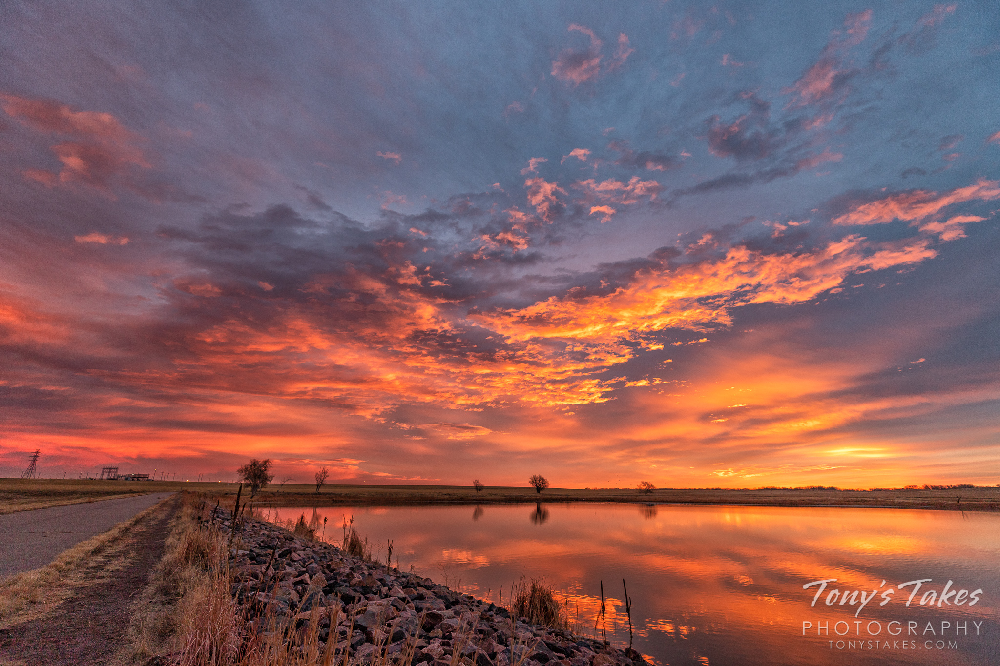 Sunrise stuns above in the sky and below in its reflection at the Rocky Mountain Arsenal. (© Tony's Takes)