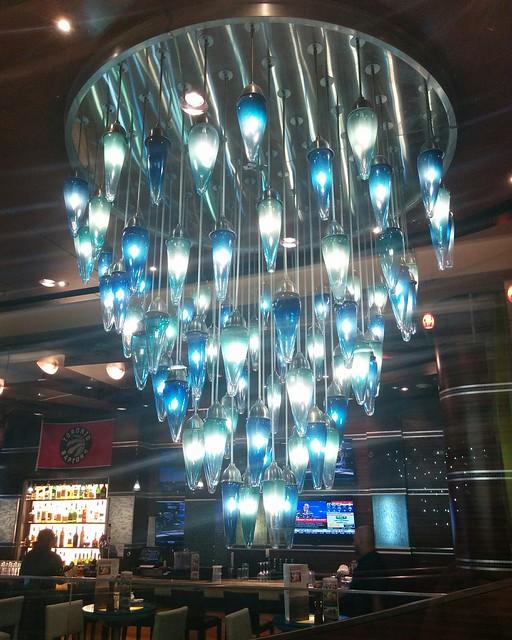 Chandelier seen through glass #toronto #picklebarrel #atriumonbay #chandelier #glass #blue #white #lights