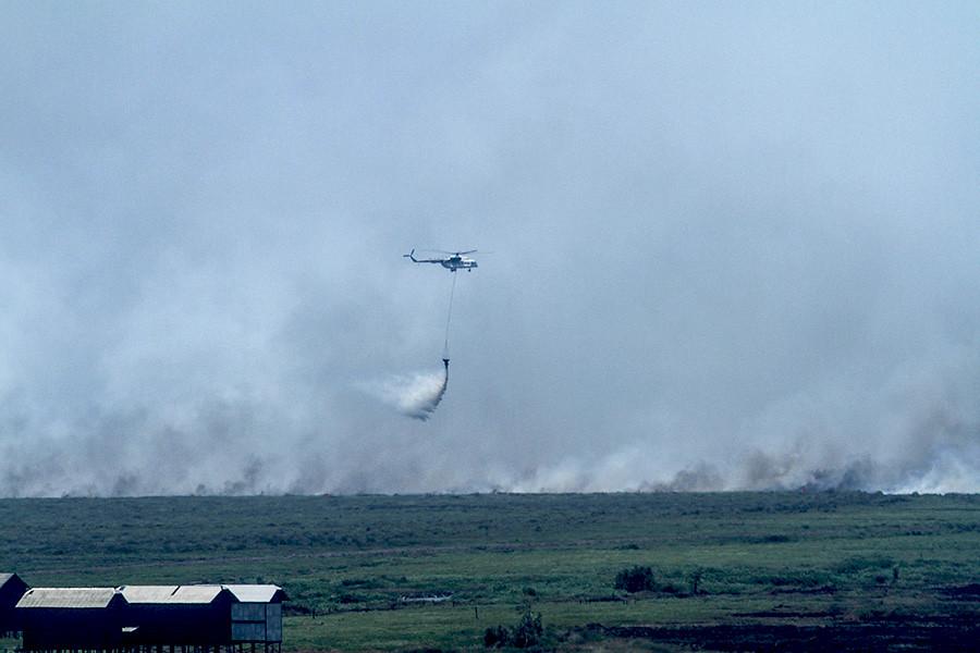 火勢蔓延Pedamaran區傳統高腳屋住宅區,直升機空投水彈試圖撲滅。