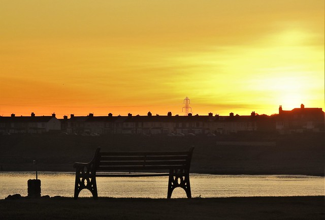 Silhouetted Seaside Seat at Sunset