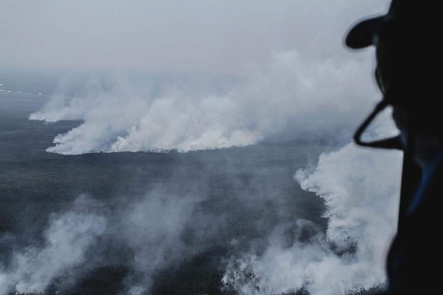 一名BPBD人員從空中監視著Ogan Ilir區泥炭地的火災。
