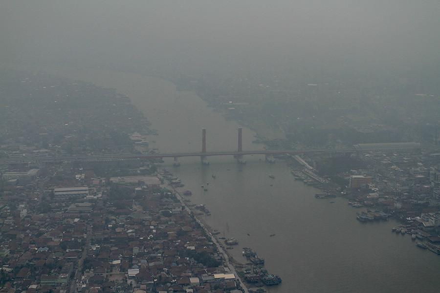 森林大火產生的濃煙籠罩南蘇門答臘首府巨港的地標,穆西河安培大橋。Nopri Ismi攝, Mongabay Indonesia提供。