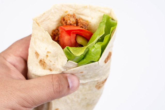 Tortilla with Minced meat Tomato and Lettuce in the hand