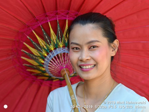 matthahnewaldphotography facingtheworld qualityphoto head face eyes beautifuleyes mouth teeth lips lipstick expression consensual conceptual travel tourism grace beauty style oriental traditional cultural folklore bosang chiangmai thailand thai asia asian person one female young woman women backdrop primelens nikond610 nikkorafs85mmf18g 85mm 4x3ratio resized 1200x900pixels horizontal street portrait closeup headshot threequarterview outdoor colour posingcamera smiling feminine beautiful attractive elegant stunning cheerful parasol umbrella oilpaperumbrella holding red lookingatcamera