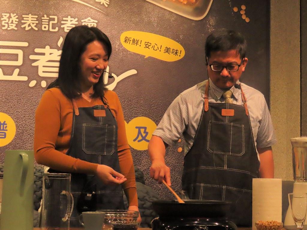 彰農米糧媽媽黃楷芸(左)與農糧署副署長蘇茂祥示範炒黑豆茶。攝影:廖靜蕙