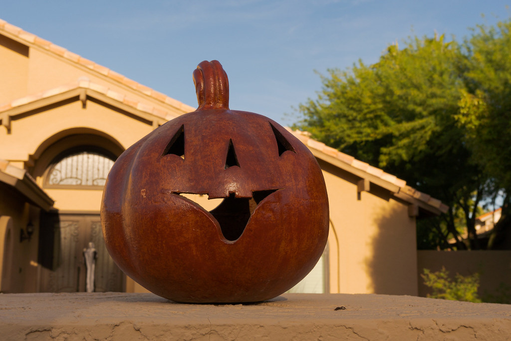 A smiling piece of pumpkin art sits on a mailbox post in front of a house in the Buenavante neighborhood of Scottsdale, Arizona in October 2018