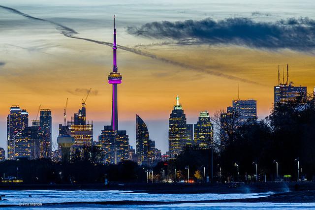Sunset over Kew Beach boardwalk and city skyline - Toronto