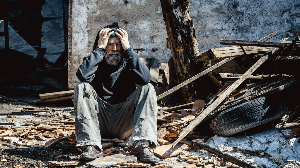 A man looking distressed in a pile of rubble