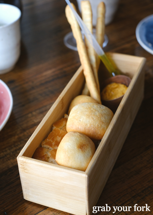 House bread box of milk bun, focaccia and breadsticks with smoked paprika butter and EVOO pipette at Noi restaurant in Petersham Sydney