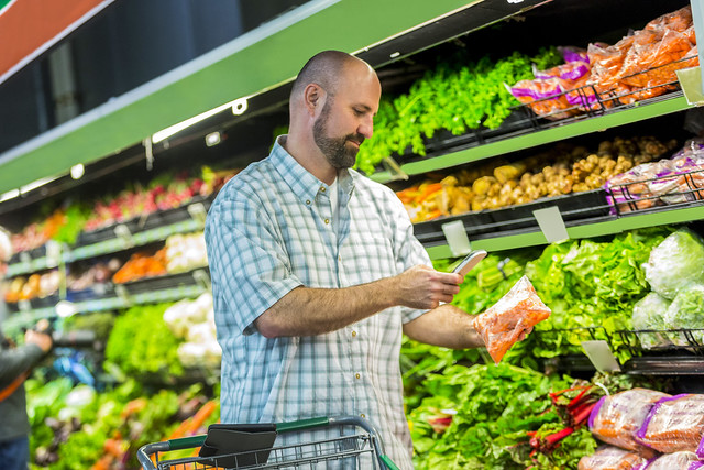A shopper checks the FNIC website for the nutrient content of vegetables