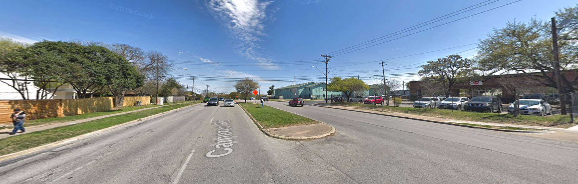 Image of Cameron Road with six travel lanes, three in each direction divided by a median, and no bicycle lanes