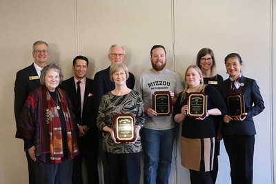 Five award recipients hold their plaques and stand alongside the directors.