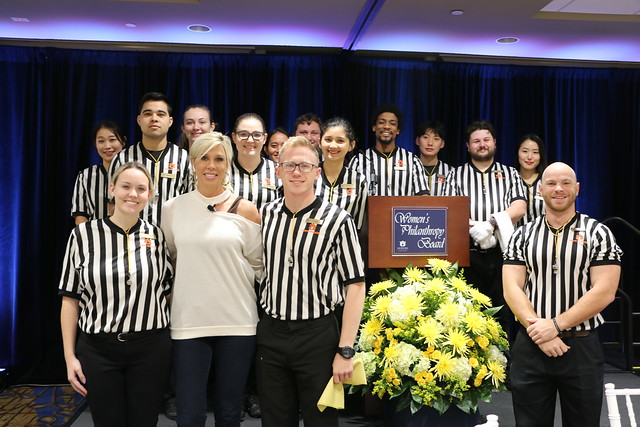 Sarah Thomas stands in a group of people wearing black and white striped sports officials' jerseys