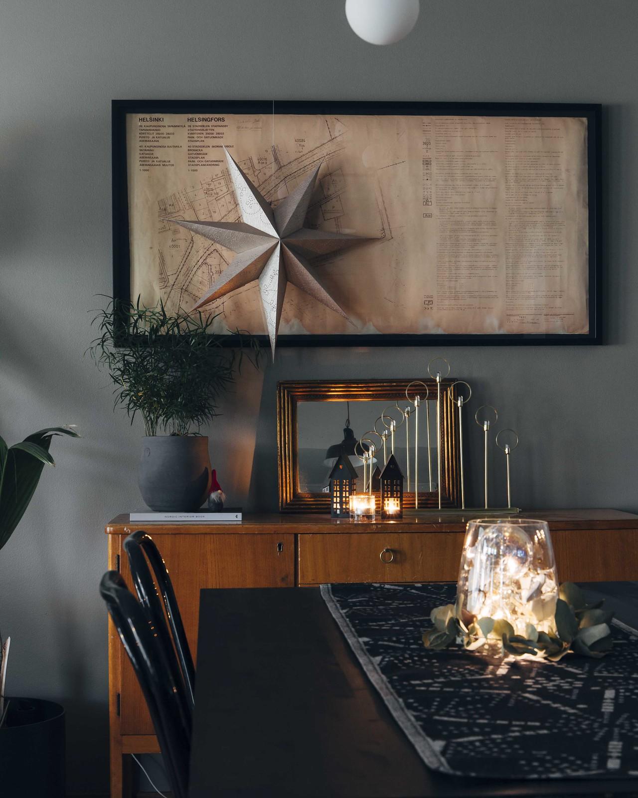 Musta ruokapöytä, jonka päällä on harmaa kaitaliina ja valosarjalla täytetty maljakko. Seinällä roikkuu kultainen paperitähti.