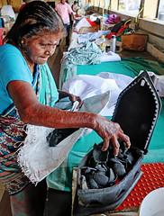 Putting charcoal in her iron - Dhobi Khana Washing Collective, Kochi, India