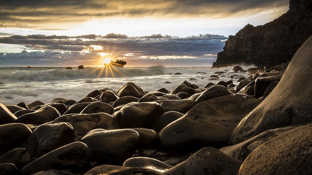 The sun raising from below the sea, over the rocky shore of the beach.