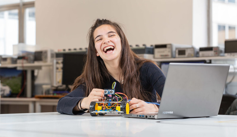 Student laughing while working on an electrical engineering component