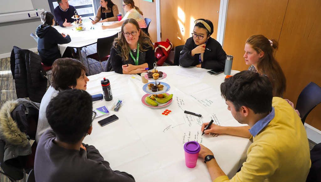 Students at a round table discussing issues and solutions with members of staff