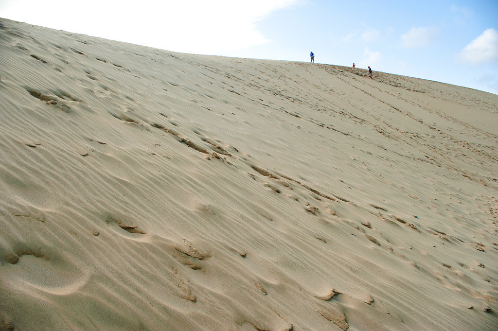 Three people walking on the top of a high sand dune