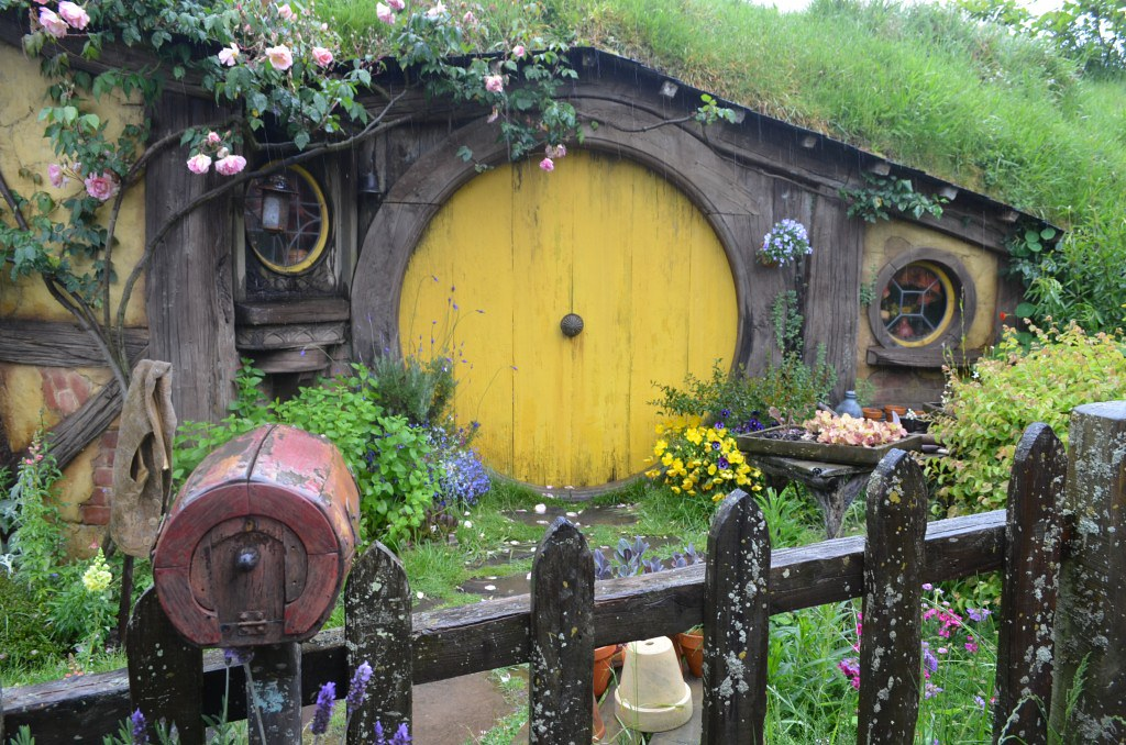 A hobbit house with a bright yellow round door. The roof is covered with moss and outside there is a red round postbox